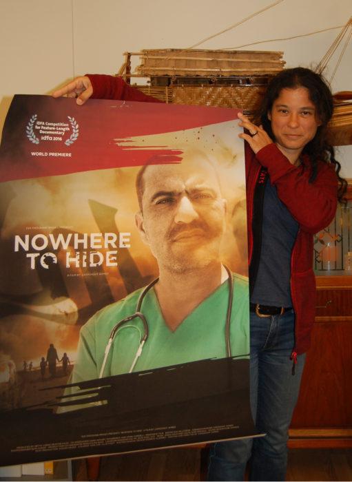 """Mette i Ten Thousand Images' lokaler i Nesoddparken holder opp posteren for filmen """"Nowhere to Hide"""" med bilde av hovedpersonen Nori Sharif. Foto: Marius M. Jenssen"""